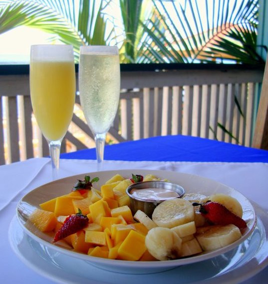 Two champagne glasses with mimosas in front of a plate of fresh fruit on a table on the patio of Lighthouse Restaurant in Roatan.