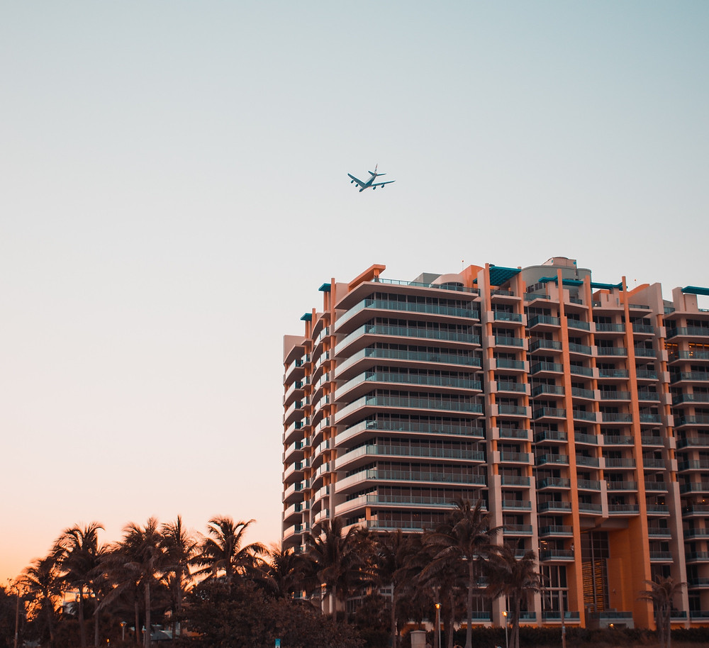 Airplane flying over a hotel that's affordable because it's near the airport