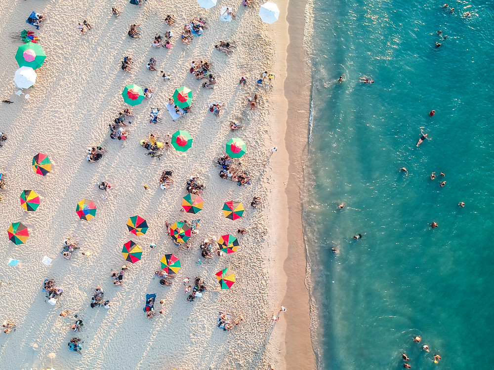 Aerial view of a beach in Florida with people and colorful umbrellas.