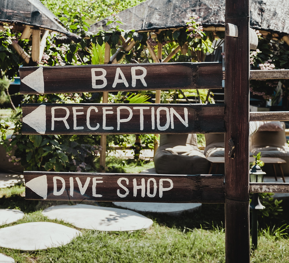 A wooden post sign in a tropical location that says bar, reception and dive shop.