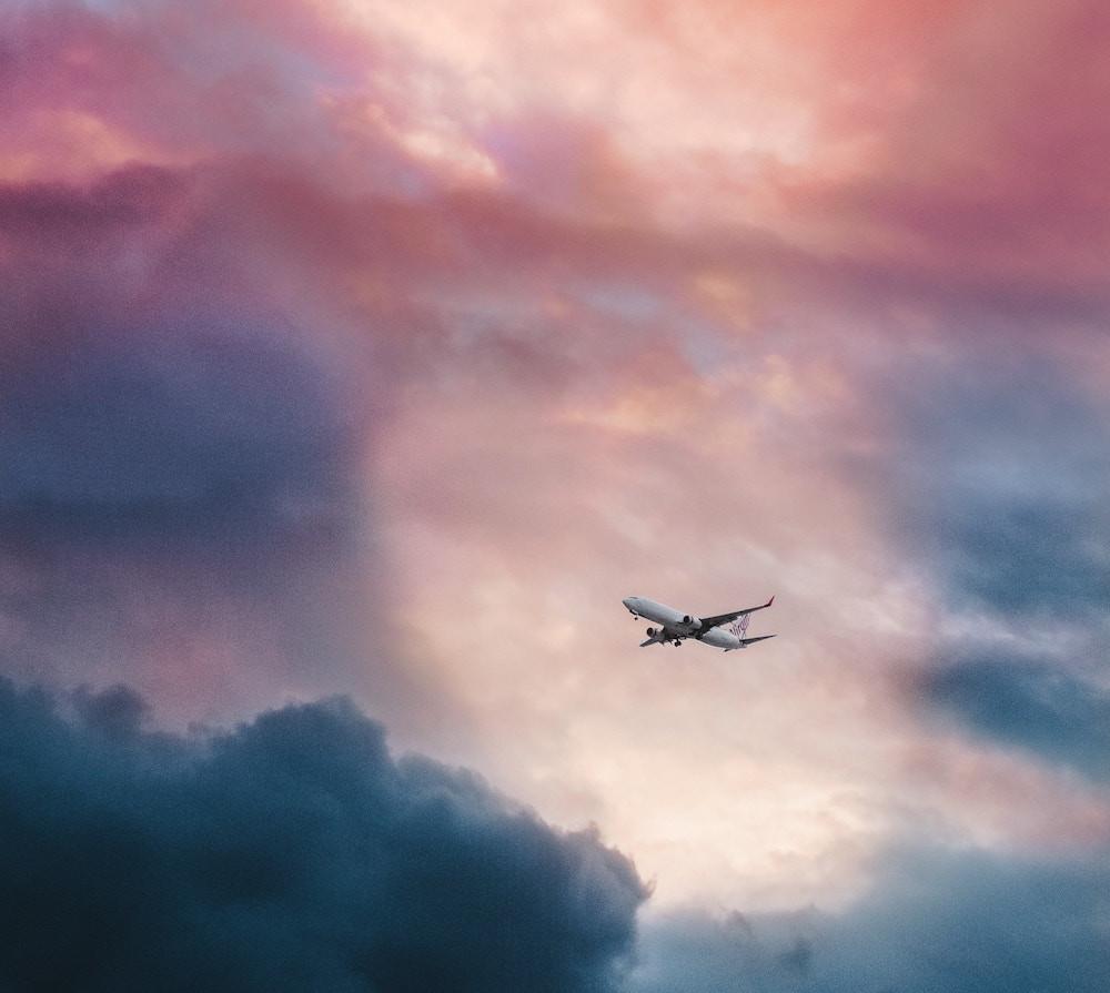 Airplane flying through sunset