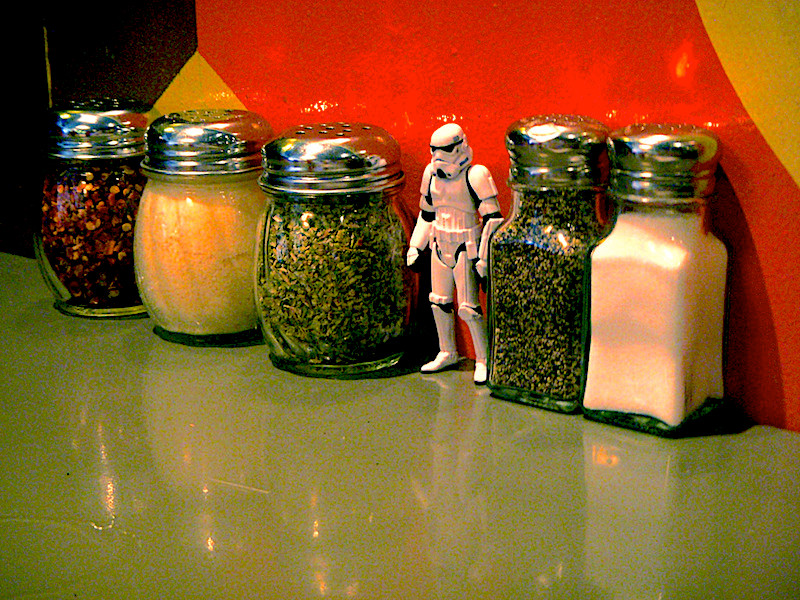 A storm trooper toy in a line with glass containers of seasoning at Home Slice in Austin.