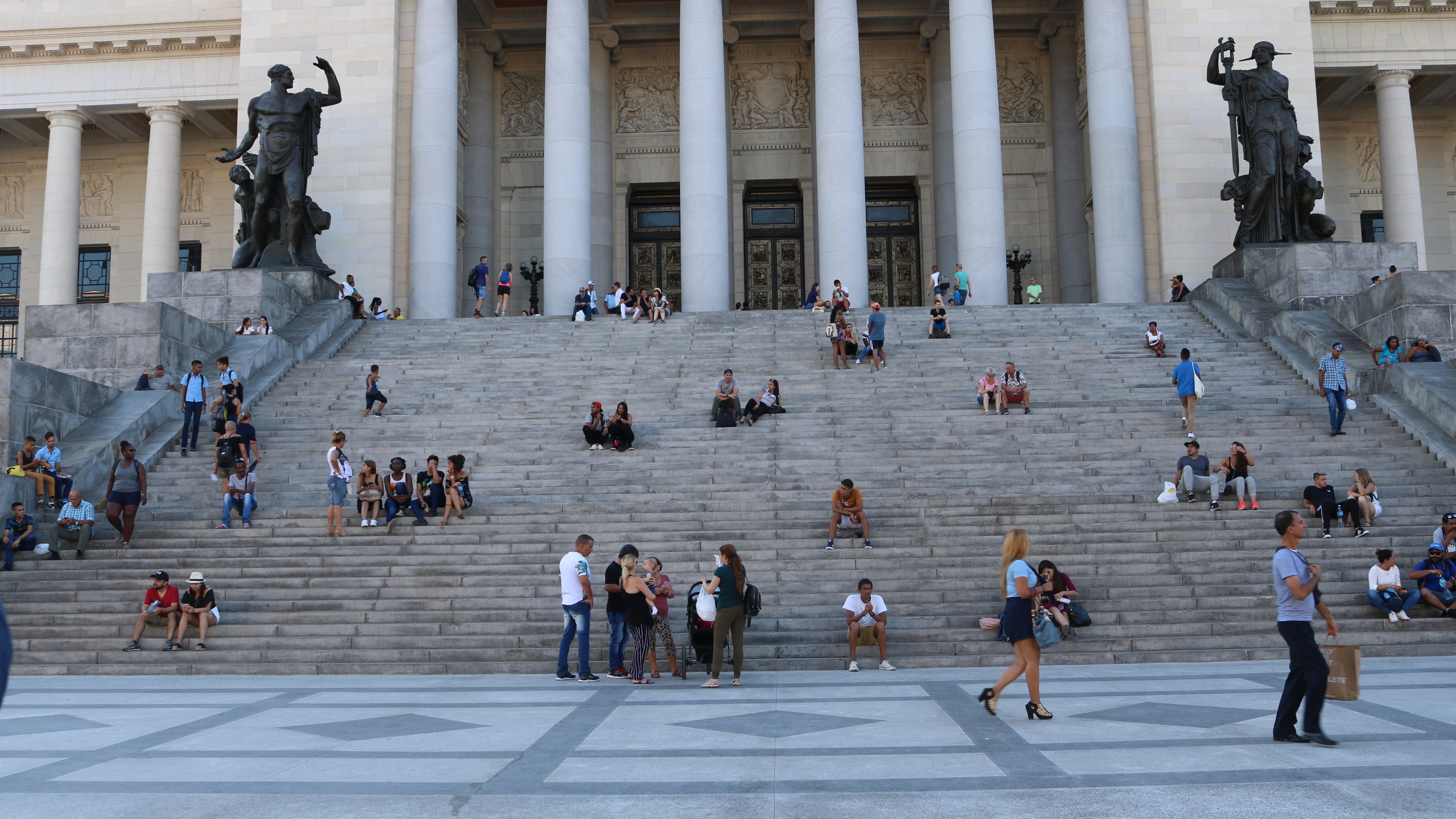 People sitting on the steps of El Capitolo in Havana, Cuba.