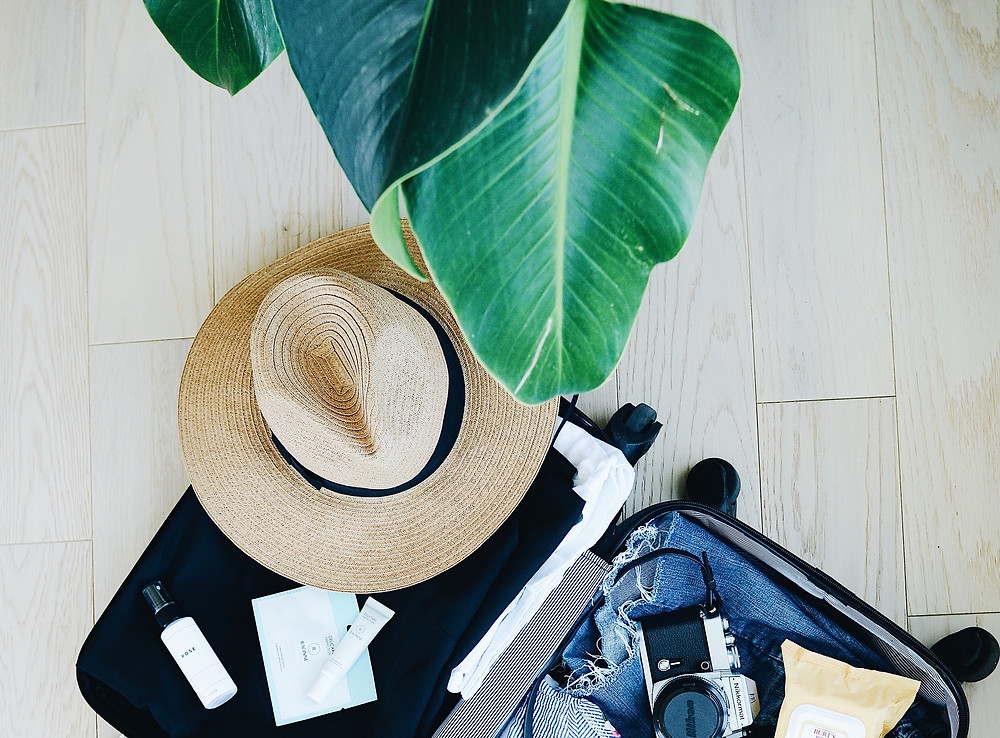 Luggage filled with all the items on a traveler's tropical packing list