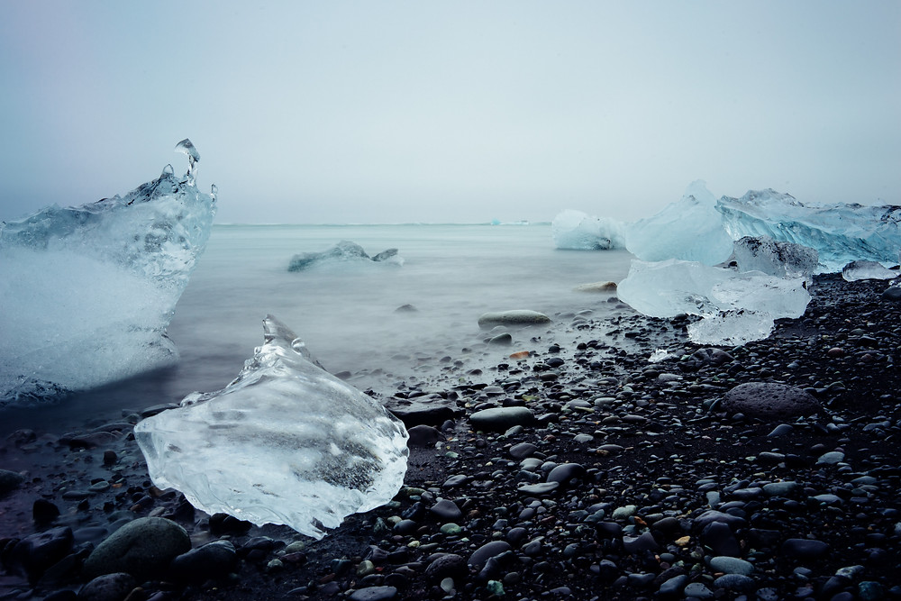 Chunks of ice on a beach covered in black pebbles.