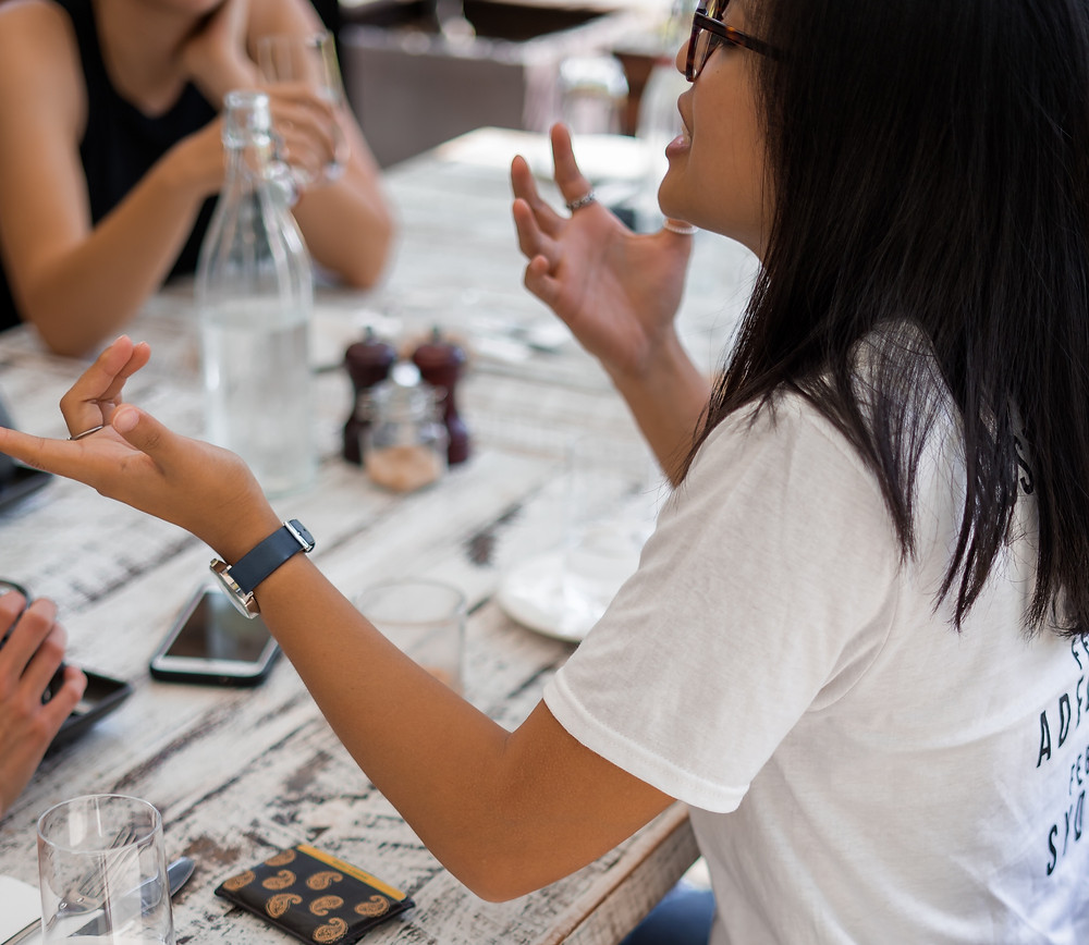 Woman in white t-shirt with glasses and a watch on talking with other people about eco-tourism