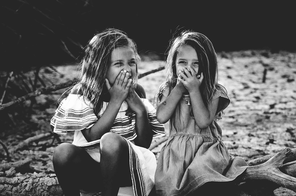 Two little girls laughing on a beach during the travel game would you rather