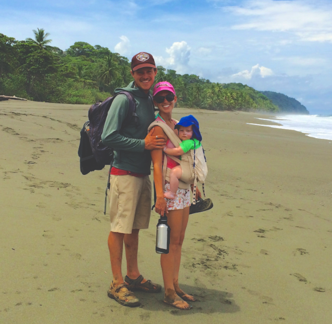 Family of three standing on a golden deserted beach in Costa Rica
