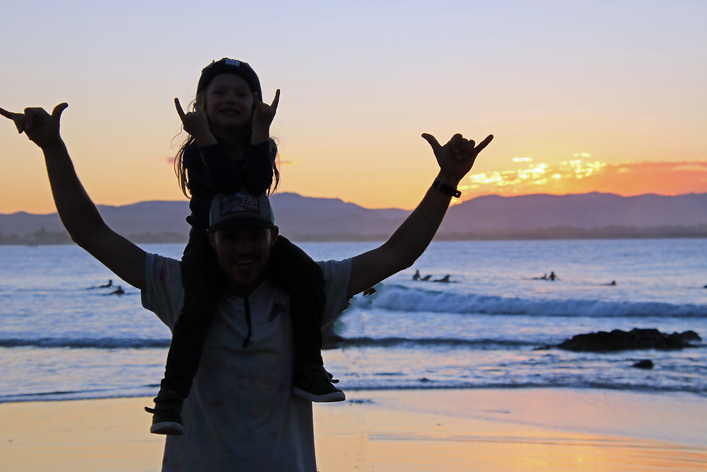 A child on a man's shoulders in front of surfers at Byron Bay Australia