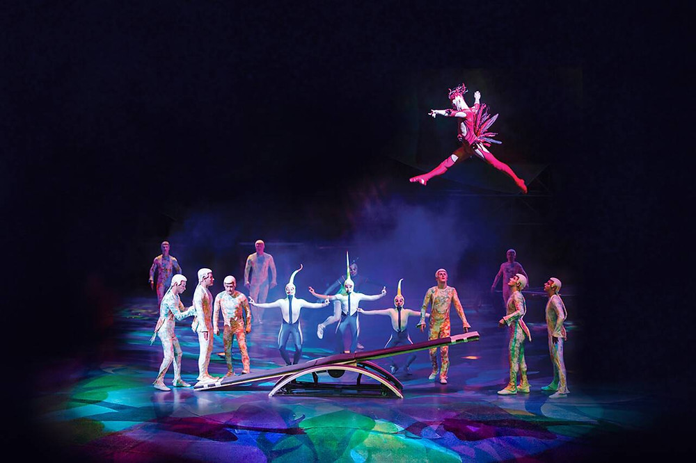 Acrobat dressed in red on seesaw in Cirque du Soleil Mystere
