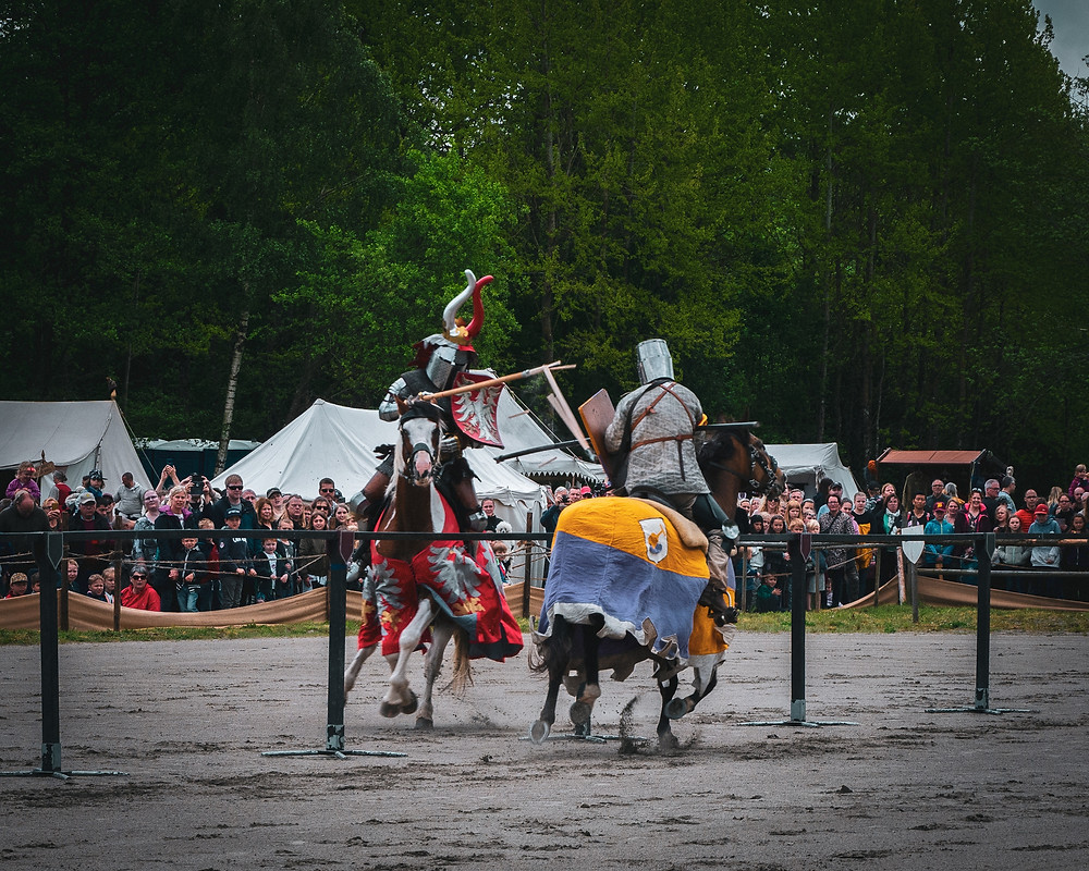 Two men on horses jousting at a Renaissance Faire