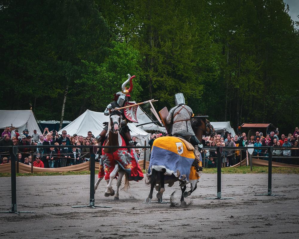 Two men on horses jousting at a Renaissance Faire
