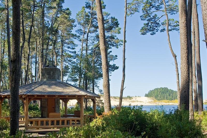 Gazebo made from logs by a lagoon and towering trees at Jesse M. Honeyman Memorial State Park in Oregon.