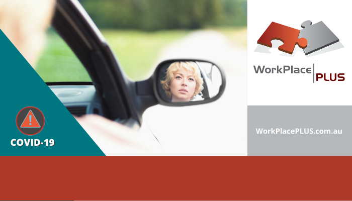 Essential worker driving, seen through side mirror. COVID-19 update for employers and employees by WorkPlacePLUS.