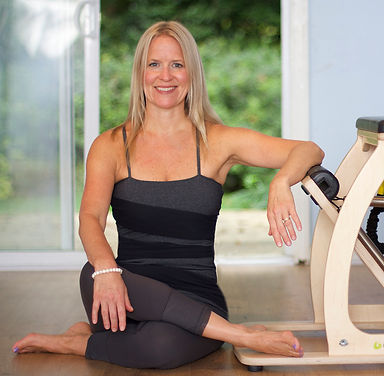 Jenn Allen sitting by Pilates Chair