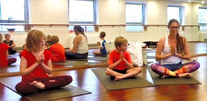 Yoga Lehrerin übt mit Kindern im Kids Yoga einfachen Haltung Sukhasana, halben Lotussitz oder Lotussitz. Hände zusammen vor Brust in Namaste. Mein inneres Licht grüßt dein inneres Licht.