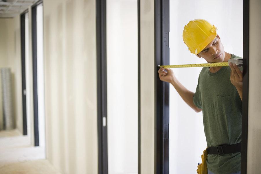 construction-worker-measuring-a-doorway-