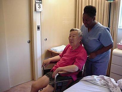 Volunteer helping elderly in wheelchair