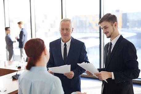 senior-businessman-talking-to-employees-