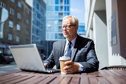 senior-businessman-with-laptop-drinking-