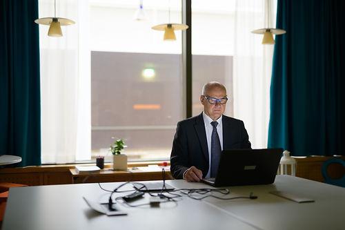 senior-businessman-using-laptop-and-sitt