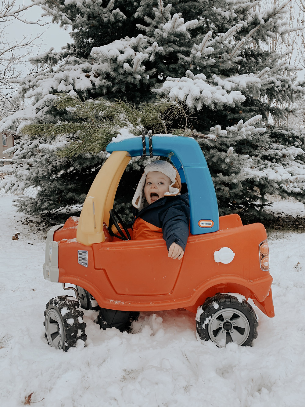Child in Little Tikes Car with Christmas Tree on top