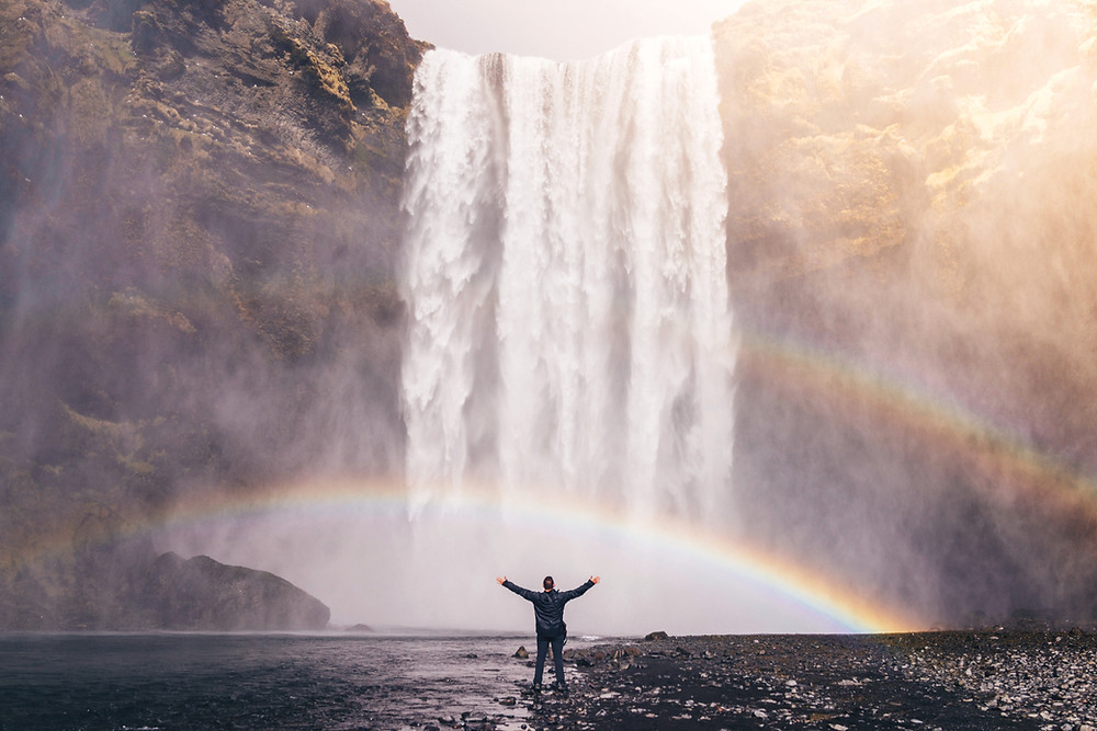 Man at the base of a waterfall and rainbow