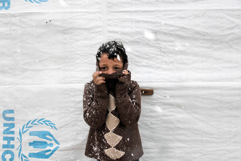 11 year old Syrian refugee Omar shields his face from the bitter cold in Lebanon's Bekaa Valley.