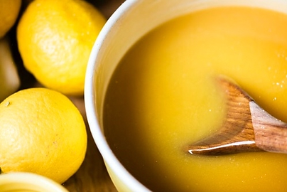 Close up of lemon curd with lemons on the side