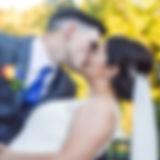 Groom kissing bride as e dips her. Veil low on head. Orange rose boutinere