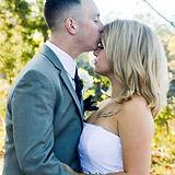 Groom kissing bride's forehead. Bride has tattoo.