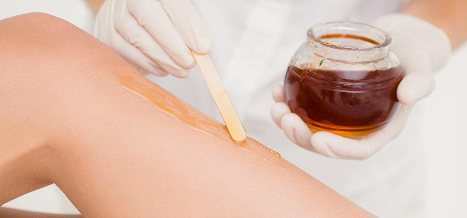Beautician applies wax to leg