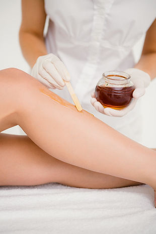 Esthetician is performing a leg wax on a client
