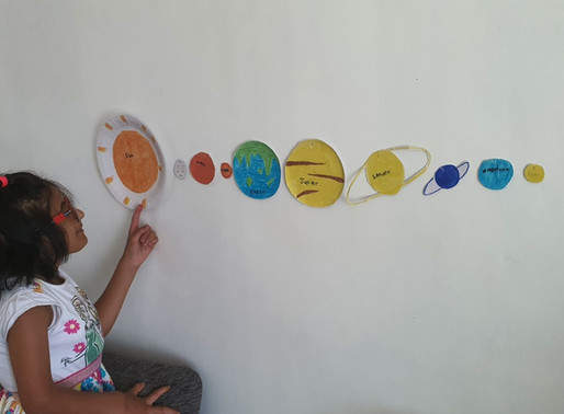 A Year 5 pupil with her fantastic model of our Solar System.