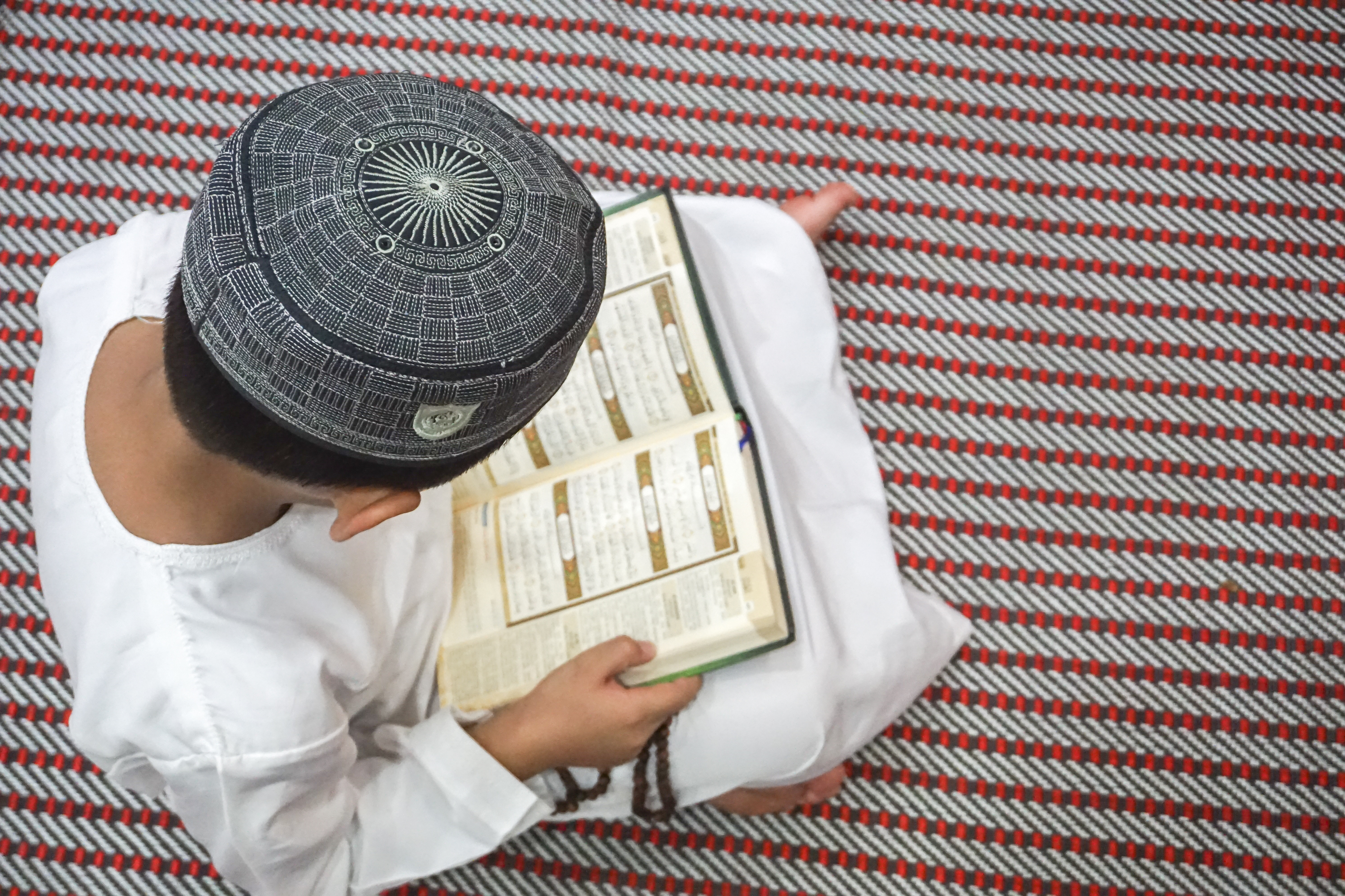 Boy reading al Quran during fasting month (Ramadhan ).jpg  DOF and copy space