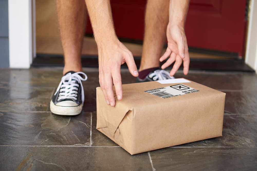 person's feet and hands reaching out to collect delivered parcel placed on the ground in front of his front door.