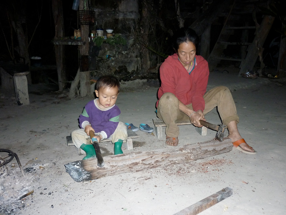 A three-year old boy and his mother sitting behind a log.  He is handling a machete and she uses a small axe.