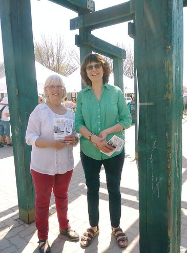 Two women handing out pamphlets at a farmers' market.
