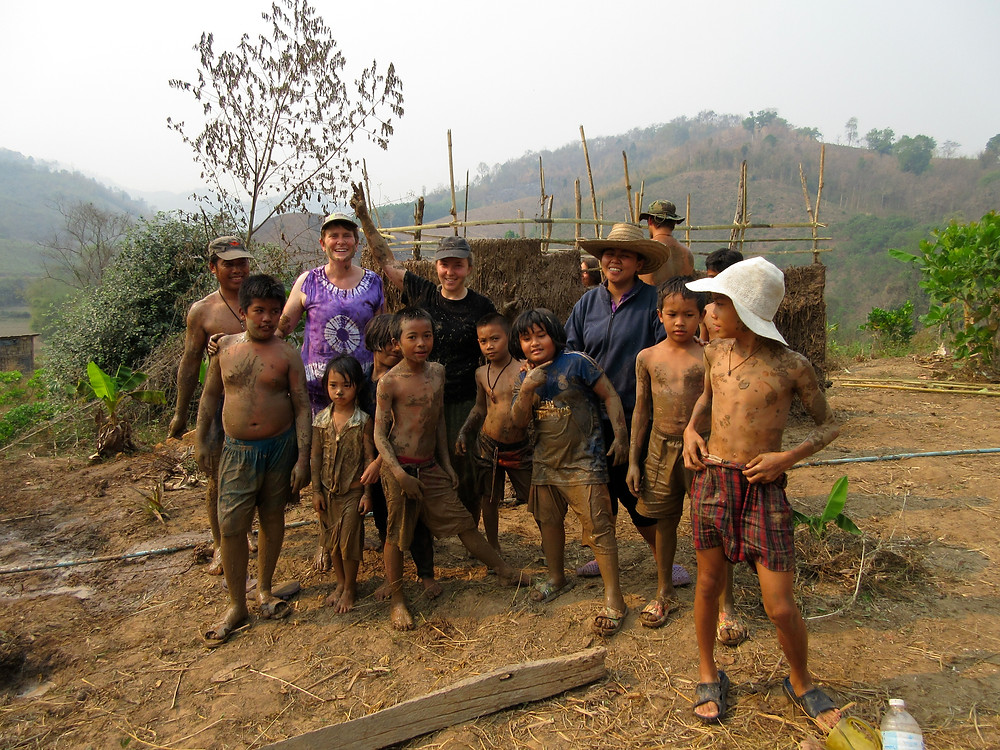 Two Thai adults, several mud-covered Thai children, and two caucasian women lined up for a picture.  A mud-covered bamboo structure is taking shape in the background.