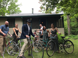 Six well-dressed adults on bikes in front of a simple cabin.