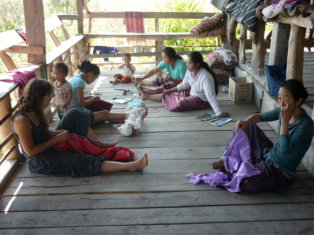 Women are sitting on the floor in an open-walled structure accomplishing various weaving and sewing related tasks.  Two children wander among them.