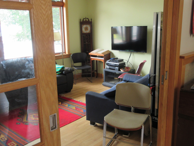 The TV room, with couches, chairs. and a large TV.