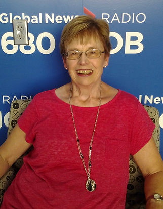 Photo of woman wearing red shirt and necklace in front of a 680 CJOB sign