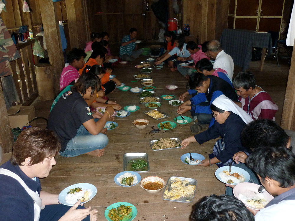 In a long hallway, people are sitting on a rustic floor.  Plates of food are laid out in the middle.