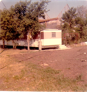 An old, beat-up mobile home with an old house being torn down in the background.