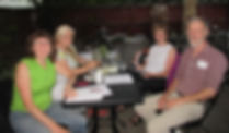 group of 4 people stting at a table having a meeting: Photo of Jeannine, Clara, Frances, & Randy