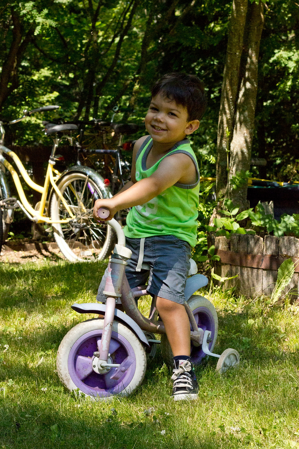 3-year old boy on a bike with training wheels.  There is such vegetation in the background.