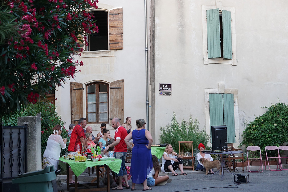 Group of about 14 people, tables, and chairs in the street in front of a European-style house.