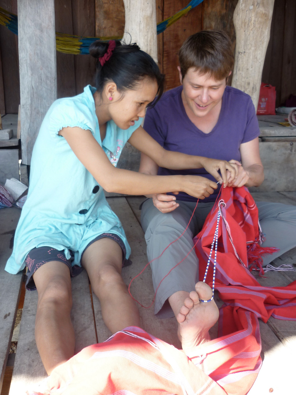 A Thai woman sits beside Jeannine on the floor, showing her how to sew a seam on a traditional piece of clothing.  A string looped around the toe helps to keep tension in the fabri.