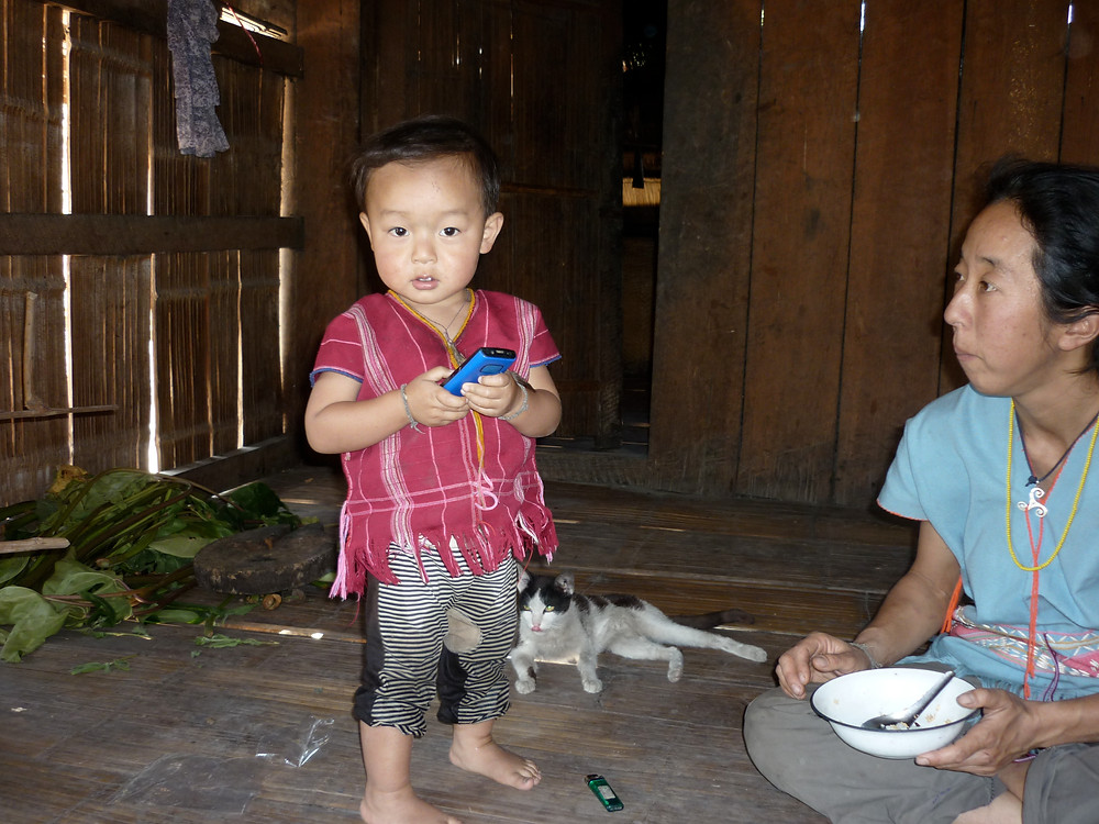 A little boy holding a cellphone stands near his mother.  Both wear colourful traditionally-woven Karen clothing.